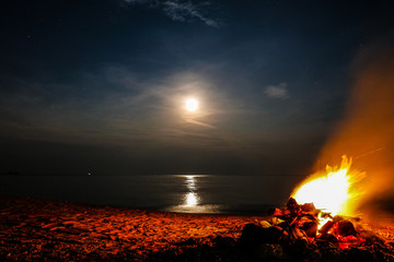 Long exposure of a full moon with bonfire on a sandy beach and ocean in the background, Khanom Beach, Thailand