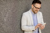 Young businessman in formal wear using mobile phone outdoor - 208151906