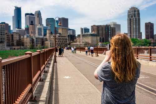Woman taking picture of city skyline © Charl