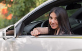 Smiling brunette girl sits at the wheel of a car and peeks out the window