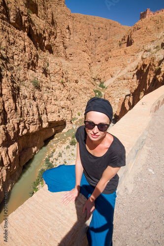 Aluminium Marokko Female tourist relaxing on winding road bank in Dades Valley, Atlas mountains, Morocco.
