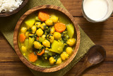 Vegan chickpea curry or chana masala with spinach, potato and carrot served in wooden bowl with lassi drink, photographed overhead with natural light (Selective Focus, Focus on the top of the curry) - 208180513