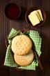 Chilenische Hallulla Brötchen in Korb, Butter und Marmelade an der Seite, fotografiert mit natürlichem Licht
