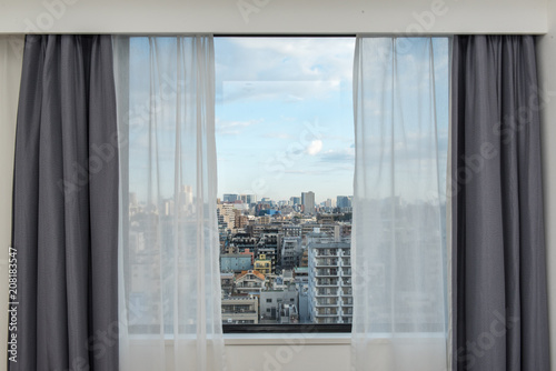 Beautiful view from the bedroom with window curtains and cityscape, blue sky, modern home decor. - 208183547