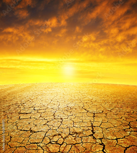 Leinwanddruck Bild Dry country with cracked soil at sunset. Global warming concept.