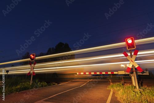 Fototapeta Langzeitbelichtung , Personenzug fährt Nachts an einer Schranke vorbei