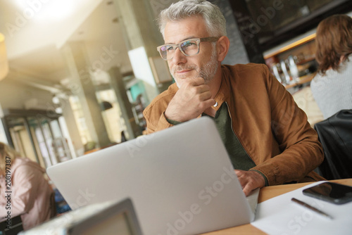 Man in trendy coffee shop working on laptop computer