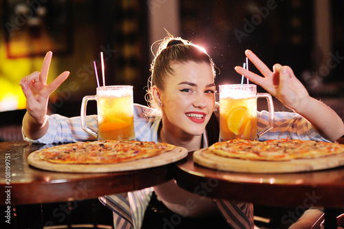 Fotobehang Pizzeria a young pretty girl eating pizza and drinking beer or a beer citrus cocktail on the background of a bar or pizzeria.