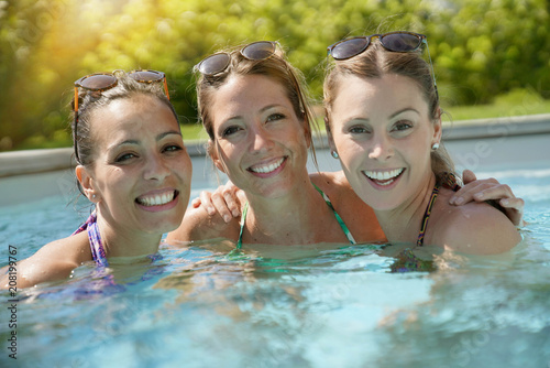 Foto Murales Girls relaxing in swimming pool, sunny day