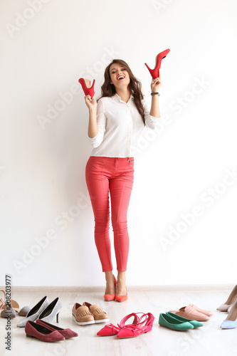 Leinwanddruck Bild Young woman with many beautiful shoes indoors