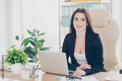Poster Portrait of cheerful positive brunette director sitting at desktop in modern work station looking at camera, expension expansion ascending equality concept