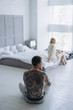 young couple sitting in bedroom separated after quarrel