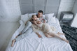 high angle view of handsome young man embracing her girlfriend from behind while lying in bed