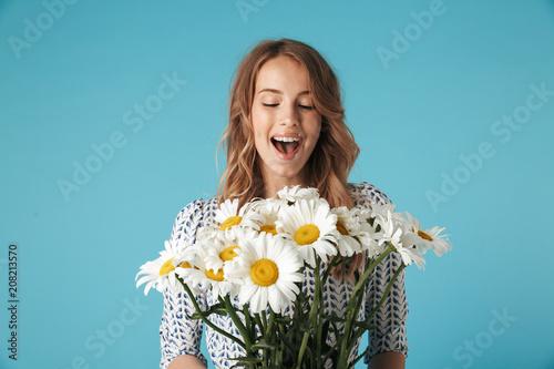 Leinwanddruck Bild Surprised happy blonde woman in dress holding bouquet of flowers