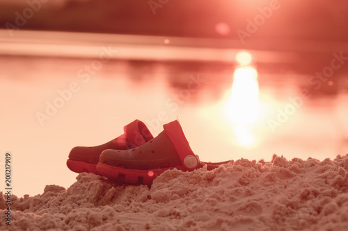 Fotobehang Koraal Child shoes on sea beach.