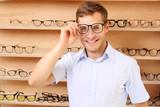 Optyk. Dobór oprawek okularowych. Mężczyzna wybiera oprawki okularowe w salonie optycznym