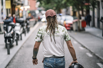 Man with dreadlocks giving his back walks through Madrid Spain. © karras6079