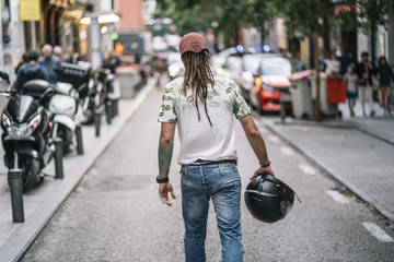 Man with dreadlocks giving his back walks through Madrid Spain.