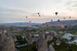 scenic view of pile of hot air balloons flying over cityscape and stone formations in Cappadocia, Turkey