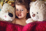Morning rise of a little girl of Caucasian appearance next to two soft bears - 208224313
