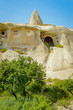 front view of trees and old stone dwelling under bright blue sky, Cappadocia, Turkey