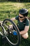 Bike repair. Young man repairing mountain bike in the field - 208228353