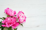 Beautiful pink peonies flowers on white wooden background. Copy space, top view. Greeting card