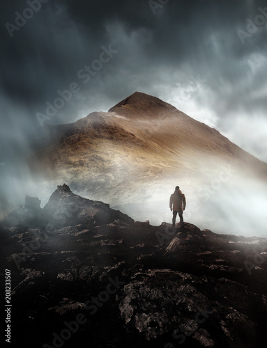 Fotobehang Grijze traf. A person hiking looks onwards at a mountain shrouded in mist and clouds with the peak visible. Scenic landscape photo composite.