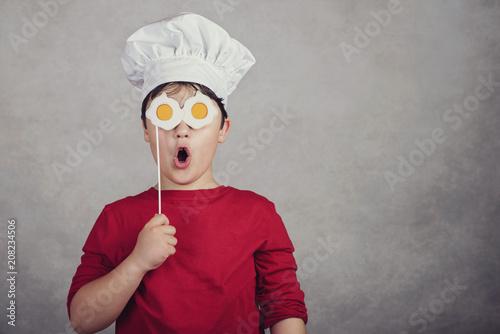 niño gracioso con huevos fritos en sus ojos - 208234506