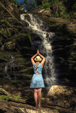 Woman in hat meditates near forest waterfall.