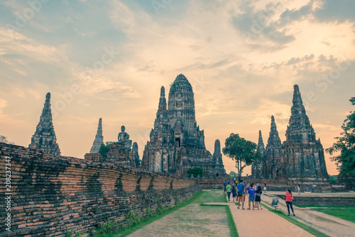 Fotobehang Boeddha Tourists at Wat Chaiwatthanaram, Buddhist temple, Ayutthaya Historical Park, Thailand, at sunset