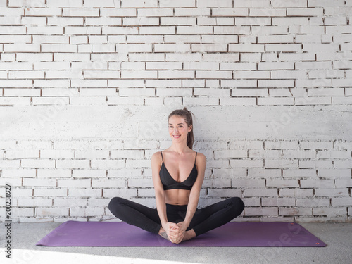 Portrait of smiling woman before exercises. Brunette with fit body on yoga mat. Healthy lifestyle and sports concept. Series of exercise poses.