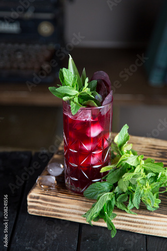 Foto Murales Red cocktail drink in a glass with mint leaves and ice, fresh juice and liquor