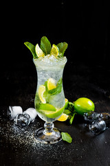 Fresh mojito with ice and lime on black background