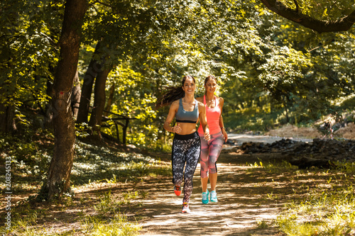 Two young woman  jogging outdoor on dirt road at the park .Green environment. - 208245133