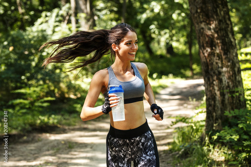 Fototapeta Young woman jogging outdoor on dirt road at the park .Green environment.