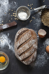Top view of whole grain bread on a dark wooden table; culinary concept.