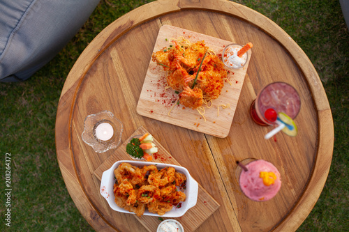 Close up to appetizer calamari and fried shrimp on tray with colourful smoothy.