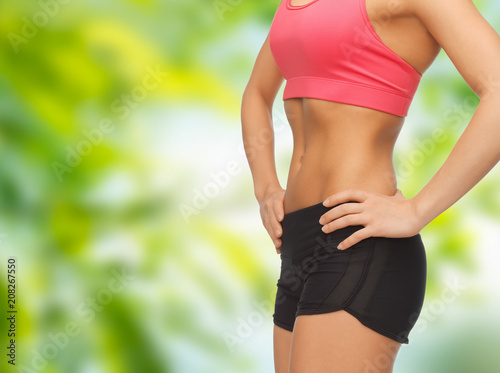 fitness, diet and slimming concept - close up of female torso and abdomen over green natural background