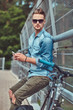 Handsome hipster with stylish haircut in sunglasses resting after riding on a bicycle, holds a smartphone.