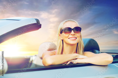 Fridge magnet travel, road trip and people concept - happy young woman in convertible car over sunset sky background