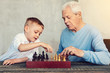 Playing chess. Attentive smart serious men of different generations playing chess while sitting at the table