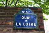 Quai de La Loire. Panneau devant un mir de briques et arbres. - 208273538