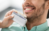 medicine, dentistry and healthcare concept - close up of dentist with tooth color samples choosing shade for male patient teeth at dental clinic