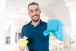 household and people concept - man in rubber gloves cleaning window with rag and spray cleaner at home - 208274936