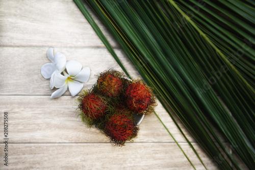 Fotobehang Plumeria Rambutan and frangipani flowers with a palm leaf. Fresh Tropical Fruits