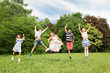 holidays, childhood and celebration concept - happy kids having fun and jumping on birthday party at summer park