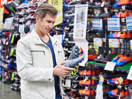 Aluminium Voetbal Man with football boots in sport store