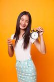 Asian woman with a clock drink orange juice. - 208277399