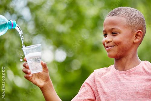 Afrykańskie dziecko trzyma plastikowe kubki
